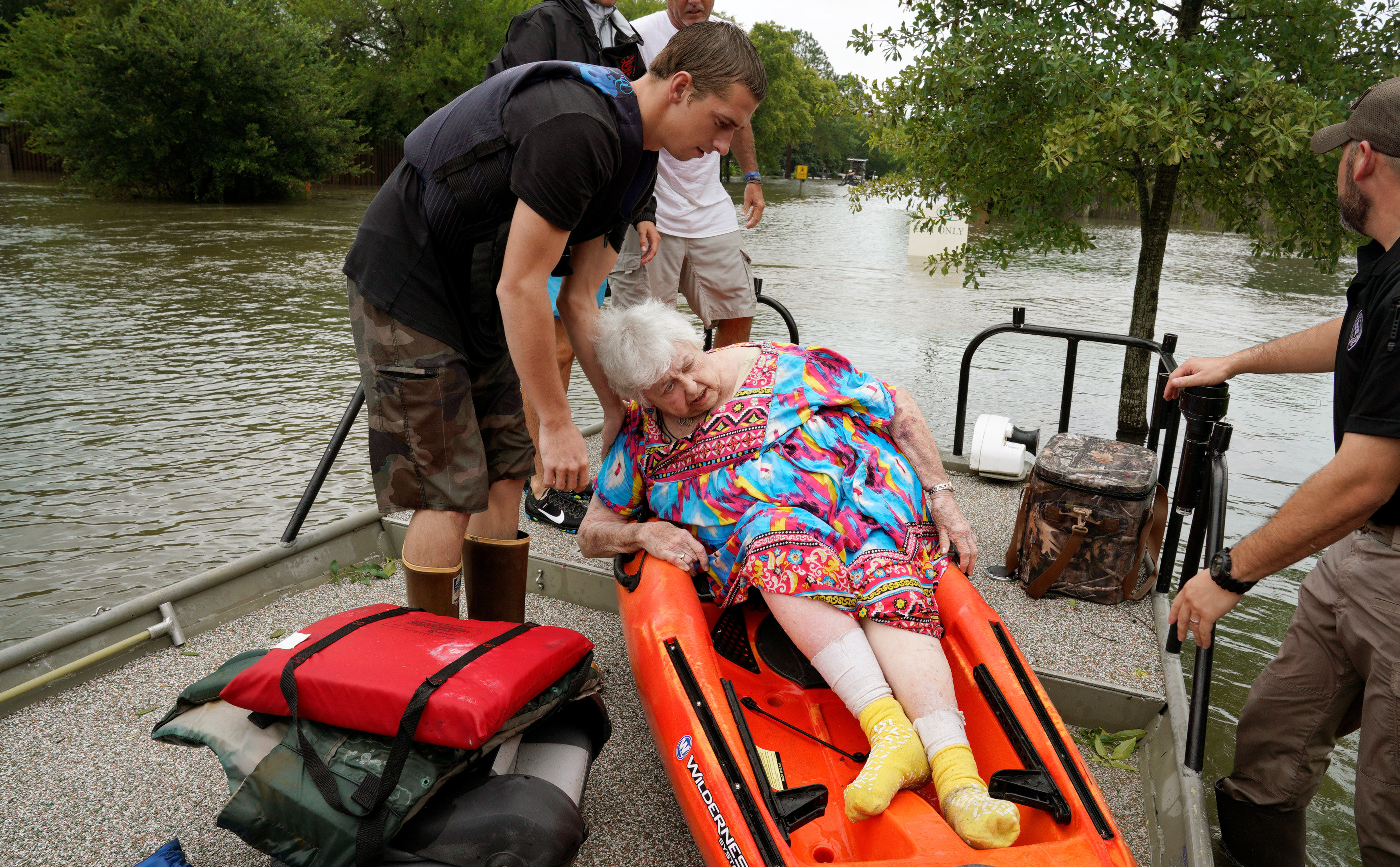 Sterling Broughton is helped from a kayak onto a rescue boat from her flooded home in Dickinson, Texas on Aug. 27, 2017. (REUTERS/Rick Wilking)