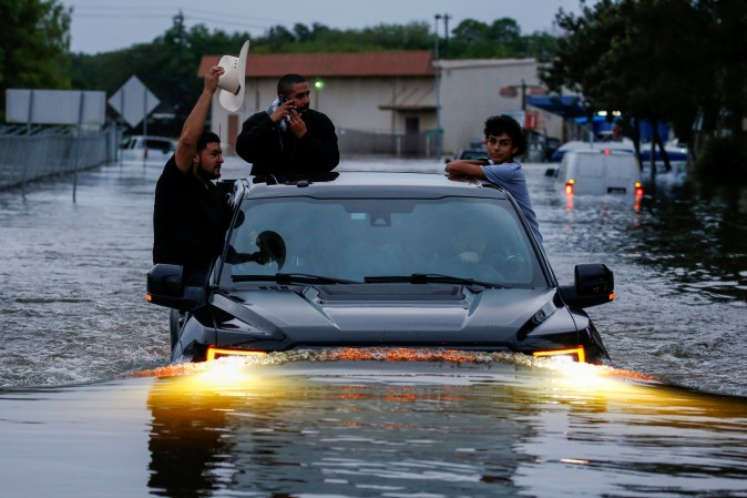 Residents use a truck to navigate through flood waters from Tropical Storm Harvey in Houston, Texas, U.S. on Aug. 27, 2017. (REUTERS/Adrees Latif)