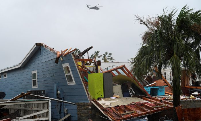 A military helicopter flies over a destroyed house.  (REUTERS/Rick Wilking)