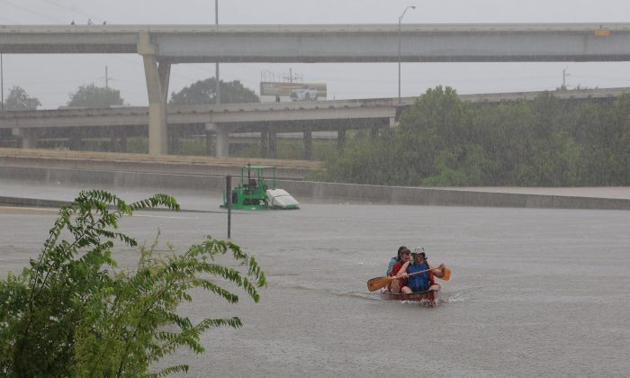 Area residents use a kayak to rescue motorists stranded on Interstate highway 45 which is submerged from the effects of Hurricane Harvey seen during widespread flooding in Houston, Texas, U.S. on Aug. 27, 2017. (REUTERS/Richard Carson)