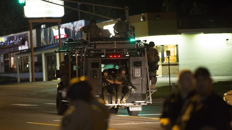 Police officers ride an armored vehicle as they patrol a street in Ferguson, Missouri on Aug. 11, 2014. (REUTERS/Mario Anzuoni)