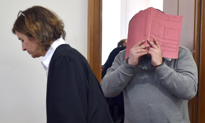 German former male nurse Niels H hides his face behind a folder as he waits next to his lawyer Ulrike Baumann (L) for the opening of another session of his trial on February 26, 2015 at court in Oldenburg, northwestern Germany. (CARMEN JASPERSEN/AFP/Getty Images)