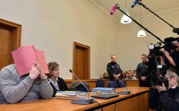 German former male nurse Niels H (L) hides his face behind a folder as he waits next to his lawyer Ulrike Baumann (2nd L) for the opening of another session of his trial on February 26, 2015 at court in Oldenburg, northwestern Germany. (CARMEN JASPERSEN/AFP/Getty Images)