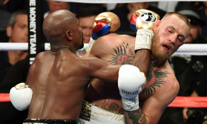 Floyd Mayweather Jr. (L) throws a punch at Conor McGregor in the fifth round of their super welterweight boxing match at T-Mobile Arena on August 26, 2017 in Las Vegas, Nevada. (Ethan Miller/Getty Images)