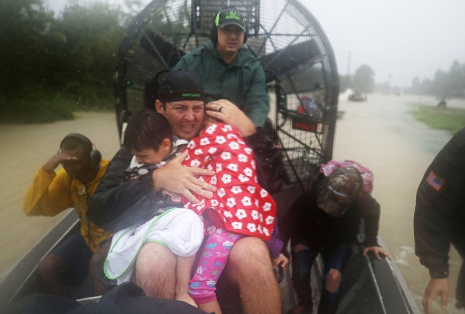 Dean Mize holds children as he and Jason Legnon use an airboat to rescue people from homes that are inundated with flooding from Hurricane Harvey on Aug. 28, 2017 in Houston, Texas. (Joe Raedle/Getty Images)