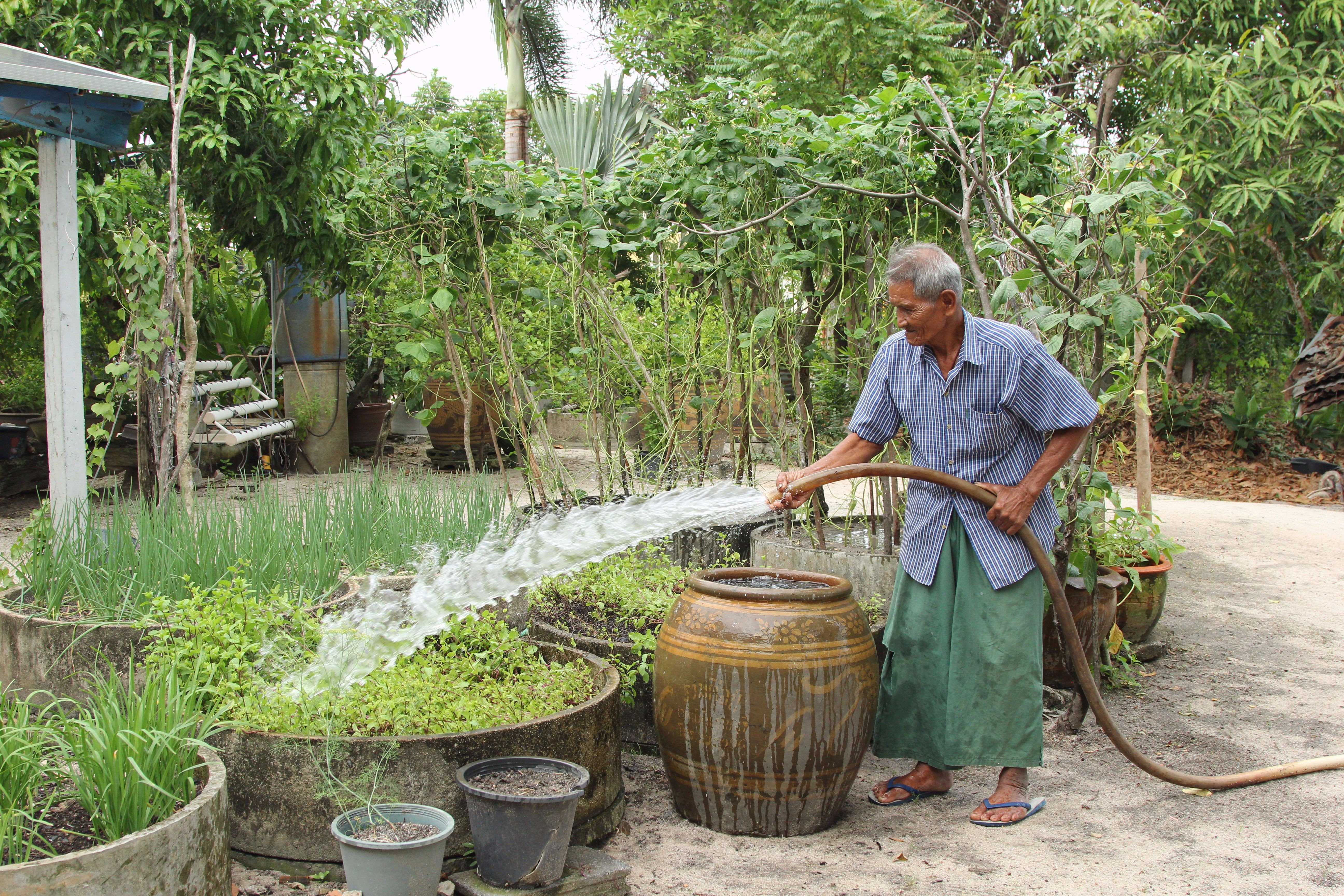 Noi Jaitang waters his garden in Map Ta Phut, Thailand, where the World Resources Institute has been working to address problems with water pollution. (Laura Villadiego)