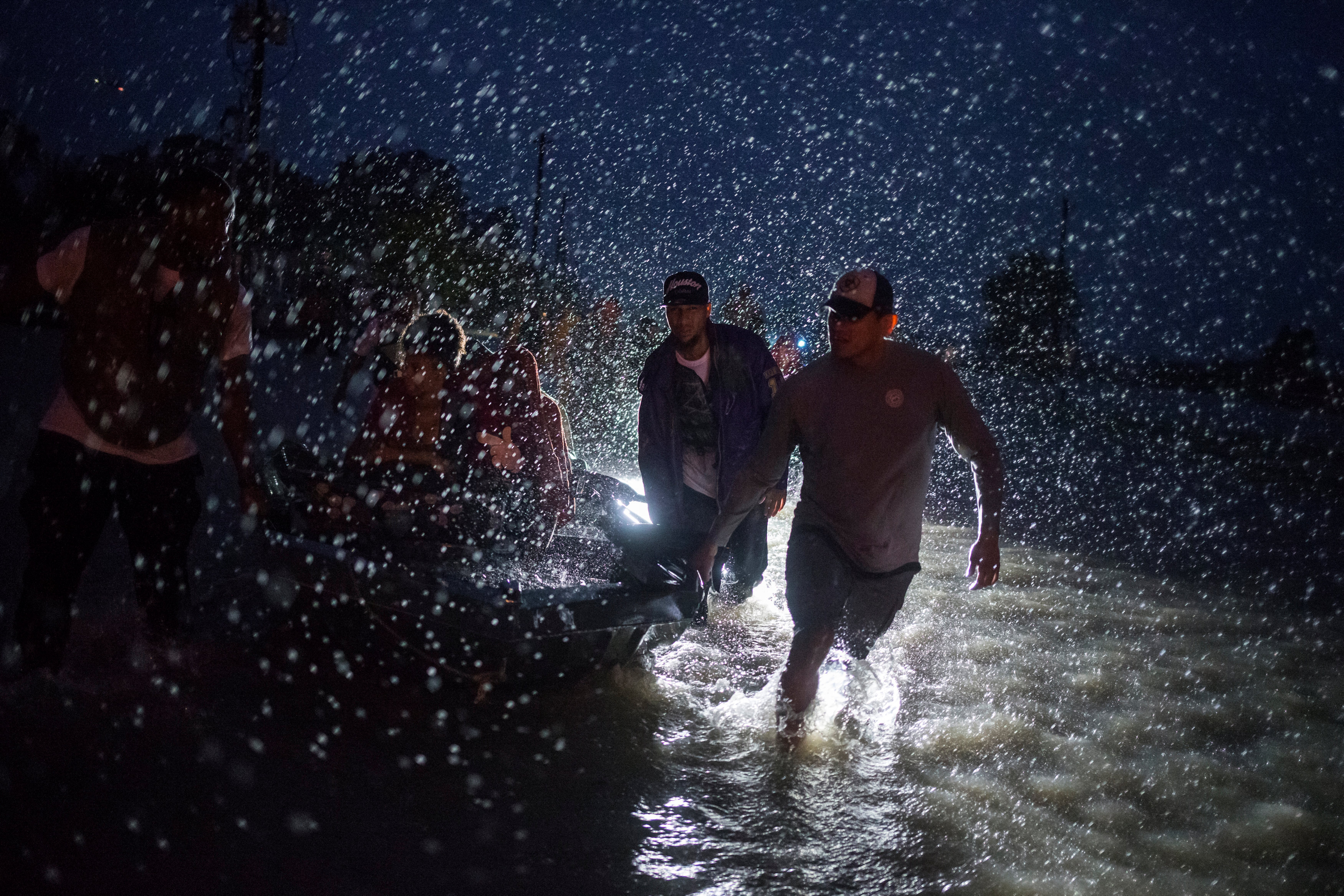 Samaritans help push a boat with evacuees to high ground during a rain storm caused by Tropical Storm Harvey along Tidwell Road in east Houston, Texas, U.S. August 28, 2017.  (REUTERS/Adrees Latif)