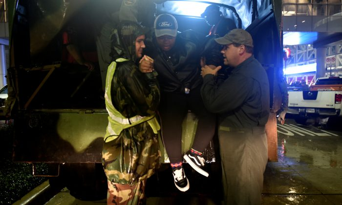 Volunteers unload evacuee Taylor Mitchell from a rescue vehicle at the George R. Brown Convention Center after Hurricane Harvey inundated the Texas Gulf coast with rain causing widespread flooding, in Houston, Texas, U.S. August 28, 2017. (Reuters/Nick Oxford)