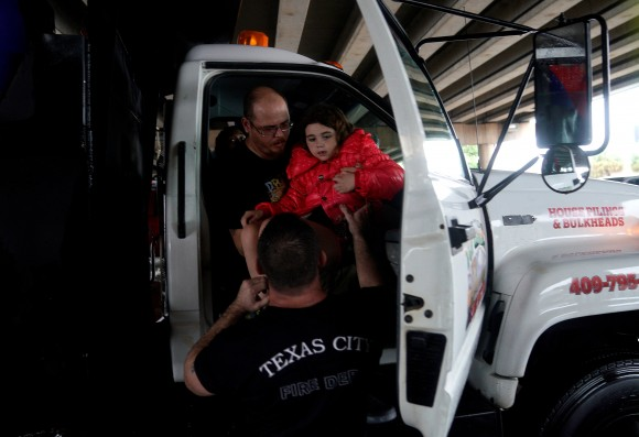 A man hands a child to Allen Jacobs, an off-duty Texas City fire fighter/paramedic, after being evacuated by dump truck from the Hurricane Harvey floodwaters in Dickinson, Texas, U.S. August 28, 2017. (REuters/Rick Wilking)