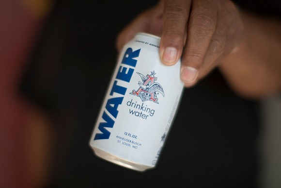 A resident holds a can of water donated by the Anheuser-Busch company as water wells supplying hundreds of residents remain dry in the fourth year of worsening drought on February 11, 2015 in East Porterville, California. Many local residents fill water tanks with free non-potable water for flushing toilets, bathing and laundering. (David McNew/Getty Images)