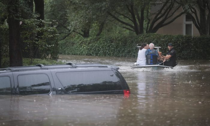Volunteers and officers from the neighborhood security patrol help to rescue residents in the upscale River Oaks neighborhood after it was inundated with flooding from Hurricane Harvey on August 27, 2017 in Houston, Texas. (Scott Olson/Getty Images)