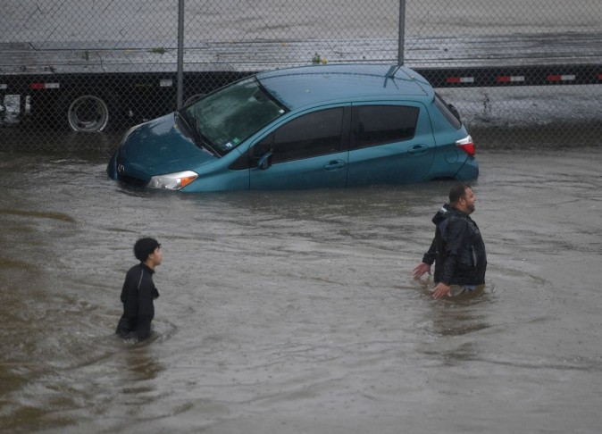 People evacuate through water past an abandoned car after Hurricane Harvey caused heavy flooding in Houston, Texas on August 28, 2017.   Rescue teams in boats, trucks and helicopters scrambled Monday to reach hundreds of Texans marooned on flooded streets in and around the city of Houston before monster storm Harvey returns. (MARK RALSTON/AFP/Getty Images)