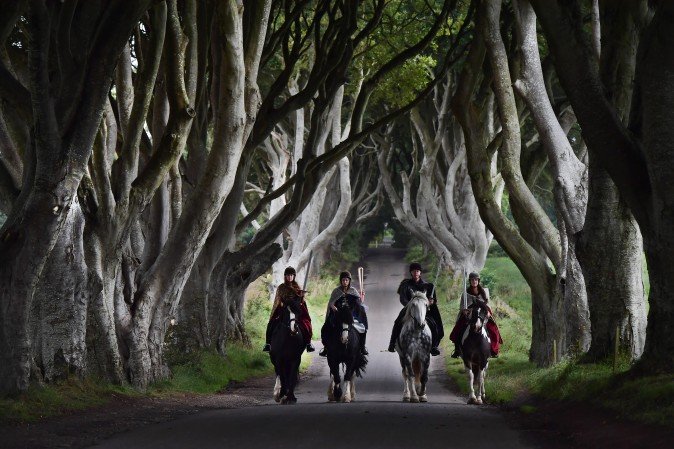 """Four actors dressed in costumes related to """"Game of Thrones"""" carry the Queen's Baton as they make their way along the Dark Hedges in Ballymoney, Northern Ireland, on Aug. 29, 2017. The Queen's Baton Relay is currently on a tour of the United Kingdom as it makes its way around Europe in preparation for the 2018 Commonwealth Games in Australia. The Dark Hedges featured as the King's Road in season two of drama series """"Game of Thrones"""" has become a tourist mecca for fans of the television series. (Charles McQuillan/Getty Images)"""