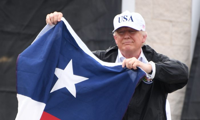 Then-President Donald Trump holds a Texas state flag outside of a fire house in Corpus Christi, Texas, on Aug. 29, 2017. (Jim Watson/AFP/Getty Images)