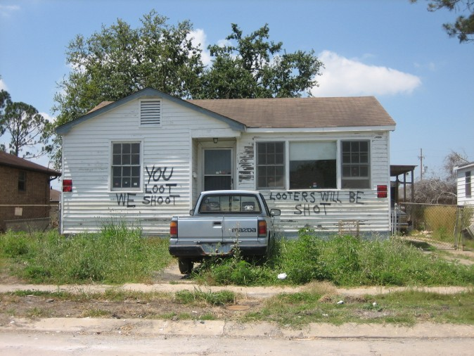 """New Orleans after Hurricane Katrina: House in formerly flooded neighborhood of Eastern New Orleans has """"You Loot We Shoot"""" notice. Mazda pickup truck out front. (Infrogmation/Wikimedia Commons)"""