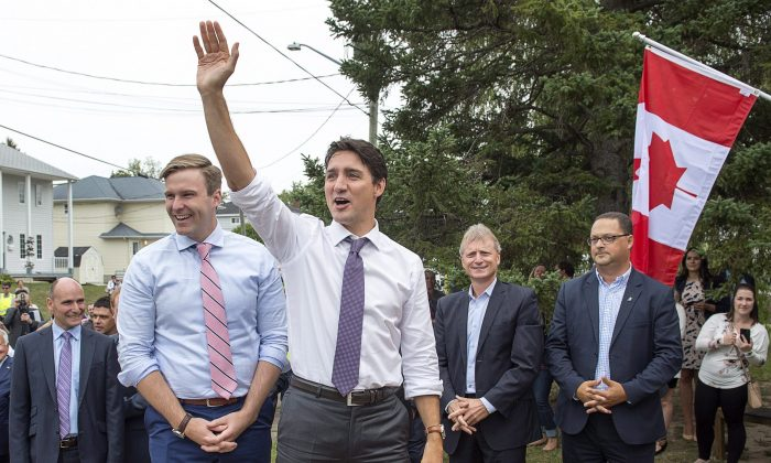 Prime Minister Justin Trudeau, accompanied by New Brunswick Premier Brian Gallant, waves to the crowd as he arrives for a visit to Wee College daycare and early learning centre in Moncton, N.B. on Aug. 30, 2017. (The Canadian Press/Andrew Vaughan)