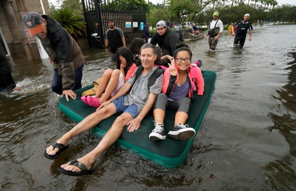 A family is evacuated on an air mattress from the Hurricane Harvey floodwaters in Houston, Texas August 29, 2017. (Reuters/Rick Wilking)