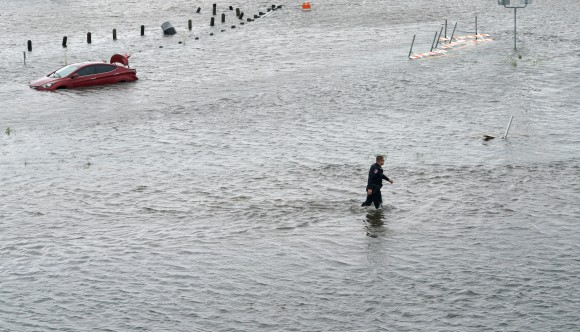A police officer wades through the Hurricane Harvey floodwaters in Alvin, Texas August 29, 2017. (Reuters/Rick Wilking)