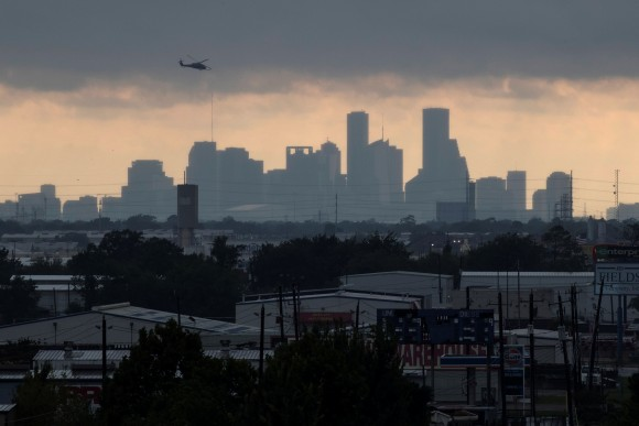 A helicopter hovers above the Houston skyline as sunlight breaks through storm clouds from Tropical Storm Harvey in Texas, U.S. August 29, 2017. (Reuters/Adrees Latif)