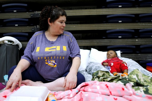 """Denise Vital, who evacuated her flooded home from Tropical Storm Harvey, watches over her 3-month-old godson at the Lake Charles Civic Center in Lake Charles, Louisiana, U.S., on August 29, 2017. Vital, who's home was destroyed by Hurricane Rita in 2005 said, """"You have to keep pushing forward."""" (Reuters/Jonathan Bachman)"""