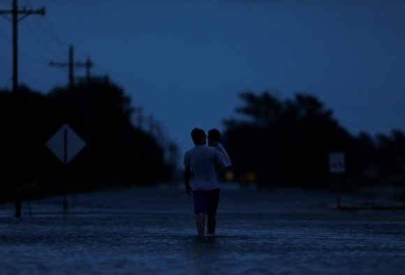 Ethan holds his 2-year-old daughter Zella as they walk through flood waters from Tropical Storm Harvey in Iowa, Calcasieu Parish, Louisiana, U.S., on August 29, 2017. (Reuters/Jonathan Bachman)