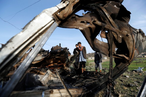 People look at the wreckage of a taxi car destroyed by a Saudi-led air strike on a checkpoint of the armed Houthi movement near Sanaa, Yemen August 30, 2017. (Reuters/Khaled Abdullah)