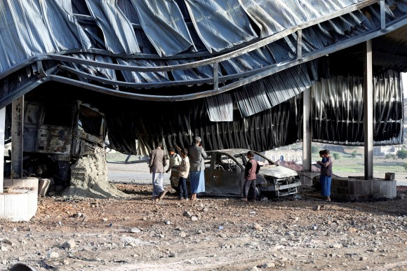 People look at a burnt car at a petrol station near a checkpoint of the armed Houthi movement hit by a Saudi-led air strike near Sanaa, Yemen August 30, 2017. (Reuters/Khaled Abdullah)