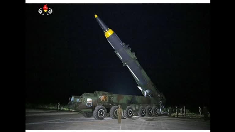 North Korean leader, Kim Jong Un (left), standing next to intermediate-range ballistic missile (IRBM) Hwasong-12 prior to launch (screenshot)