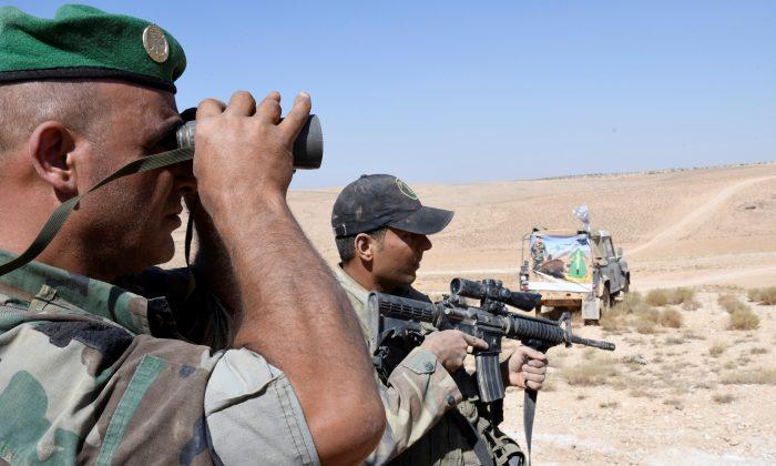 A Lebanese Army soldier looks through binoculars in Ras Baalbek, Lebanon August 28, 2017. (Reuters/ Hassan Abdallah)