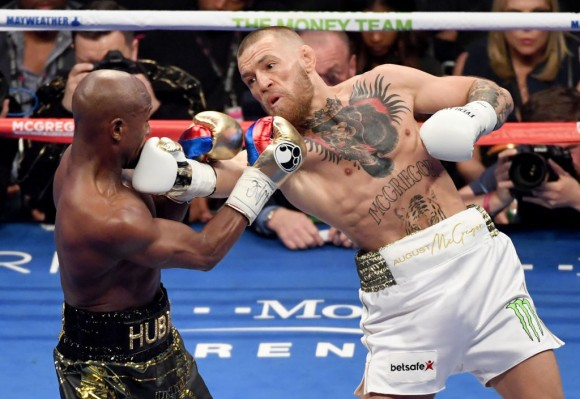 Conor McGregor (R) throws a right at Floyd Mayweather Jr. in the second round of their super welterweight boxing match at T-Mobile Arena on August 26, 2017 in Las Vegas, Nevada. Mayweather won by 10th-round TKO.  (Photo by Ethan Miller/Getty Images)