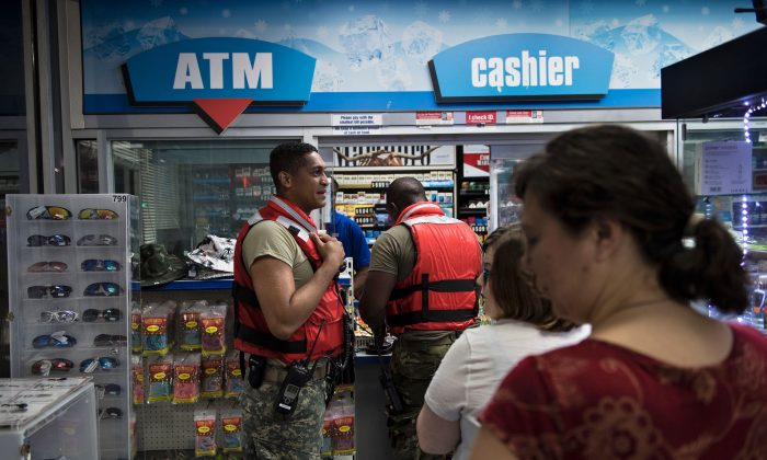 Members of the National Guard and others wait to pay at a gas station during the aftermath of Hurricane Harvey in Houston, Texas on Aug. 28, 2017. (BRENDAN SMIALOWSKI/AFP/Getty Images)