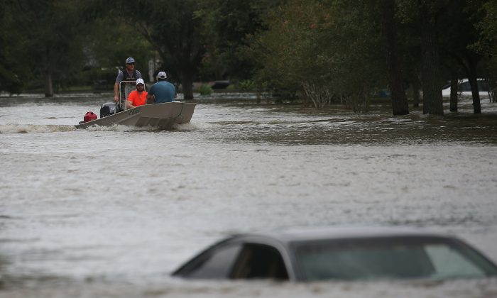 A rescue boat evacuates people from the rising waters of Buffalo Bayou following Hurricane Harvey in a neighborhood west of Houston, Texas, U.S., August 30, 2017.  Vehicles quicly become death traps in flood conditions, warn authorities. REUTERS/Carlo Allegri