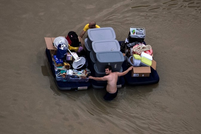 Residents wade with their belongings through flood waters brought by Tropical Storm Harvey in Northwest Houston, Texas, U.S. August 30, 2017.  (REUTERS/Adrees Latif)