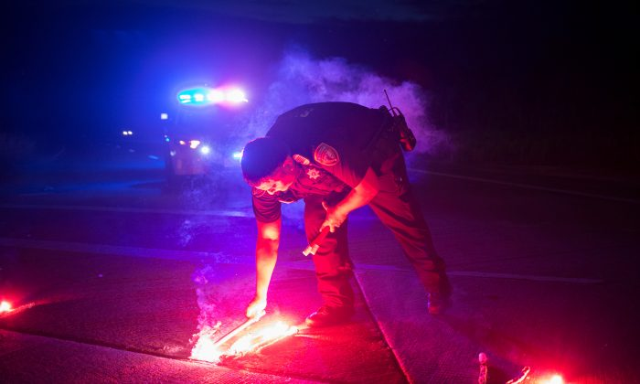 A police officer lays down a safety flare while blocking the road leading to the Arkema SA plant which was hit by floods caused Tropical Storm Harvey near Crosby, Texas on Aug. 31, 2017. (REUTERS/Adrees Latif)