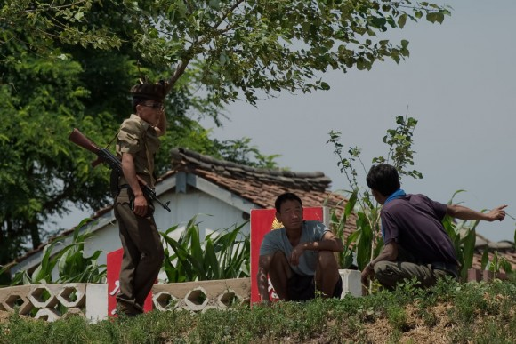 A North Korean soldier speaks with North Korean farmers as they stand on the banks of the Yalu river near Sinuiju, opposite the Chinese border city of Dandong on July 5, 2017. (NICOLAS ASFOURI/AFP/Getty Images)