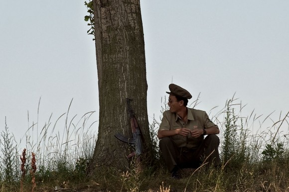A North Korean soldier takes a break and sits near a tree on the banks of the Yalu river near Sinuiju, opposite the Chinese border city of Dandong on July 5, 2017. (NICOLAS ASFOURI/AFP/Getty Images)