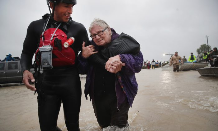 Barb Davis, 74. is helped to dry land after being rescued from her flooded neighborhood after it was inundated with rain water, remnants of Hurricane Harvey, on August 28, 2017 in Houston, Texas. (Scott Olson/Getty Images)