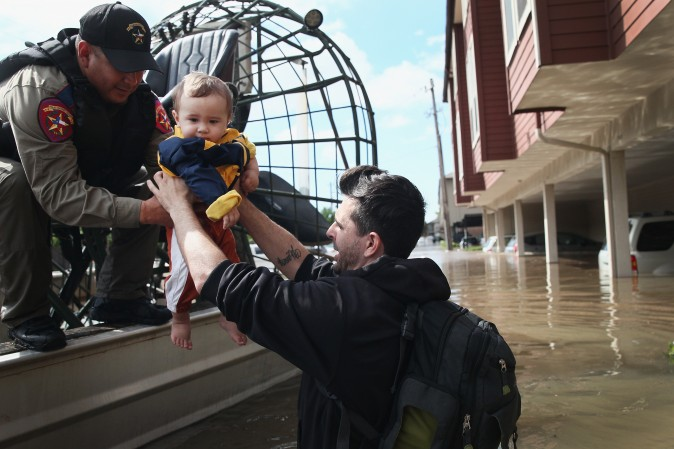 Michael Boyd passes his son Skylar over to a rescue worker as they are evacuated on an airboat from their apartment complex after it was inundated with water following Hurricane Harvey on August 30, 2017 in Houston, Texas. (Scott Olson/Getty Images)