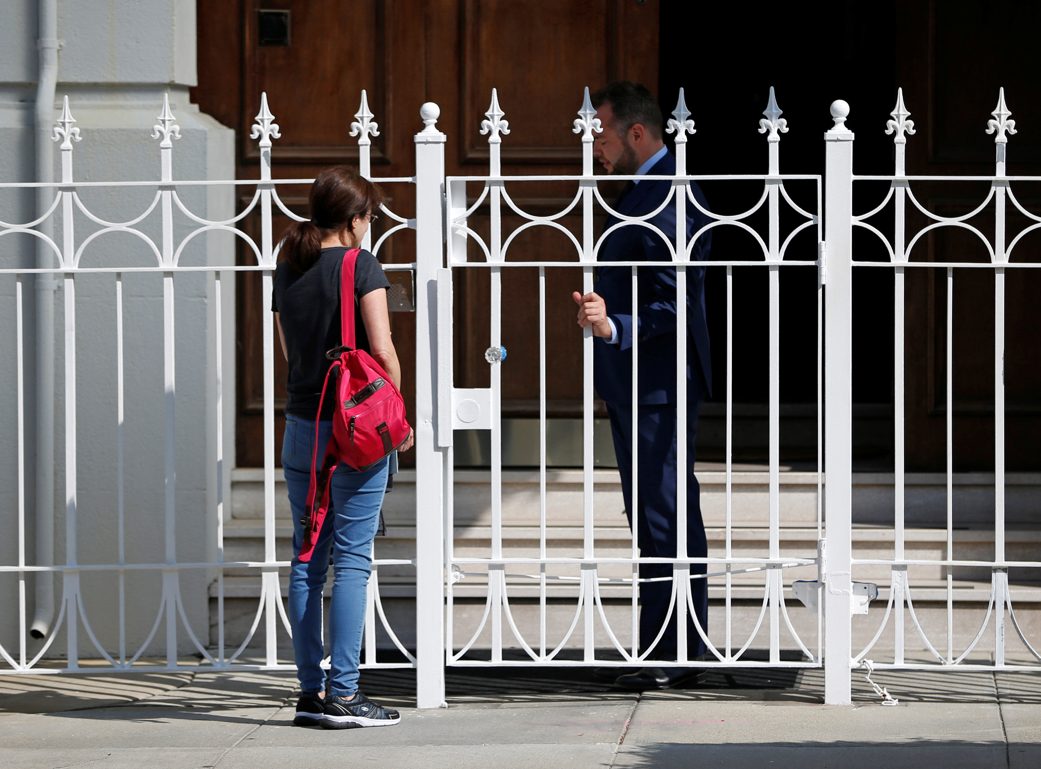 An unidentified woman talks with a man outside the gate at the entrance to the building of the Consulate General of Russia in San Francisco, Calif., on Aug. 31, 2017.   (REUTERS/Stephen Lam)