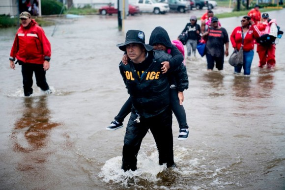 People walk to a Harris County Sheriff air boat while escaping a flooded neighborhood during the aftermath of Hurricane Harvey on August 29, 2017 in Houston, Texas. Hurricane Harvey has set what forecasters believe is a new rainfall record for the continental United States, officials said Tuesday. (BRENDAN SMIALOWSKI/AFP/Getty Images)