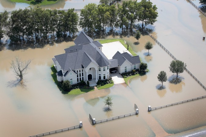 A mansion surrounded by floodwater after torrential rains pounded Southeast Texas is seen on August 31, 2017 near Sugar Land, Texas. While tempting for looters, law enforcement agencies are pledging increased penalties and determined prosecutions for crimes like looting and burglary committed in the wake of Hurricane Harvey. (Scott Olson/Getty Images)