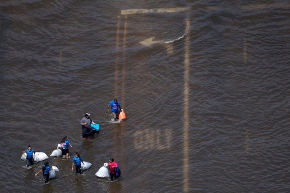 A group of people carry supplies through flood waters caused by Tropical Storm Harvey in Port Arthur, Texas, U.S. August 31, 2017. (REUTERS/Adrees Latif)