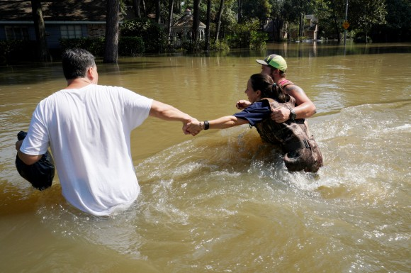 Melissa Ramirez (C) struggles against the current flowing down a flooded street helped by Edward Ramirez (L) and Cody Collinsworth as she tried to return to her home for the first time since Harvey floodwaters arrived in Houston, Texas, U.S. September 1, 2017. (REUTERS/Rick Wilking)