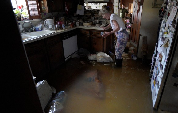 Nancy McBride collects items from her flooded kitchen as she returned to her home for the first time since Harvey floodwaters arrived in Houston, Texas September 1, 2017. (REUTERS/Rick Wilking)
