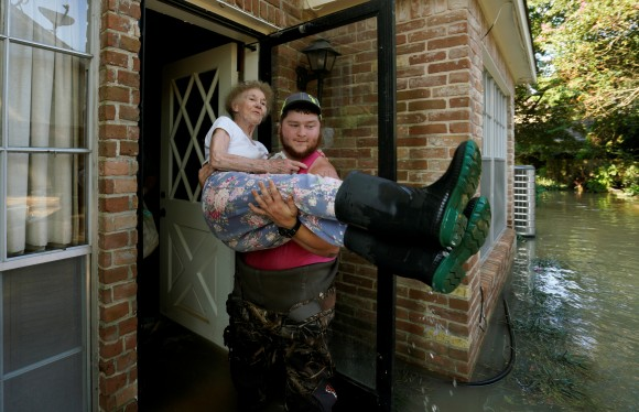 Nancy McBride is carried out of her flooded home by volunteer Cody Collinsworth, after returning home for the first time since Harvey floodwaters arrived in Houston, Texas September 1, 2017. (REUTERS/Rick Wilking)