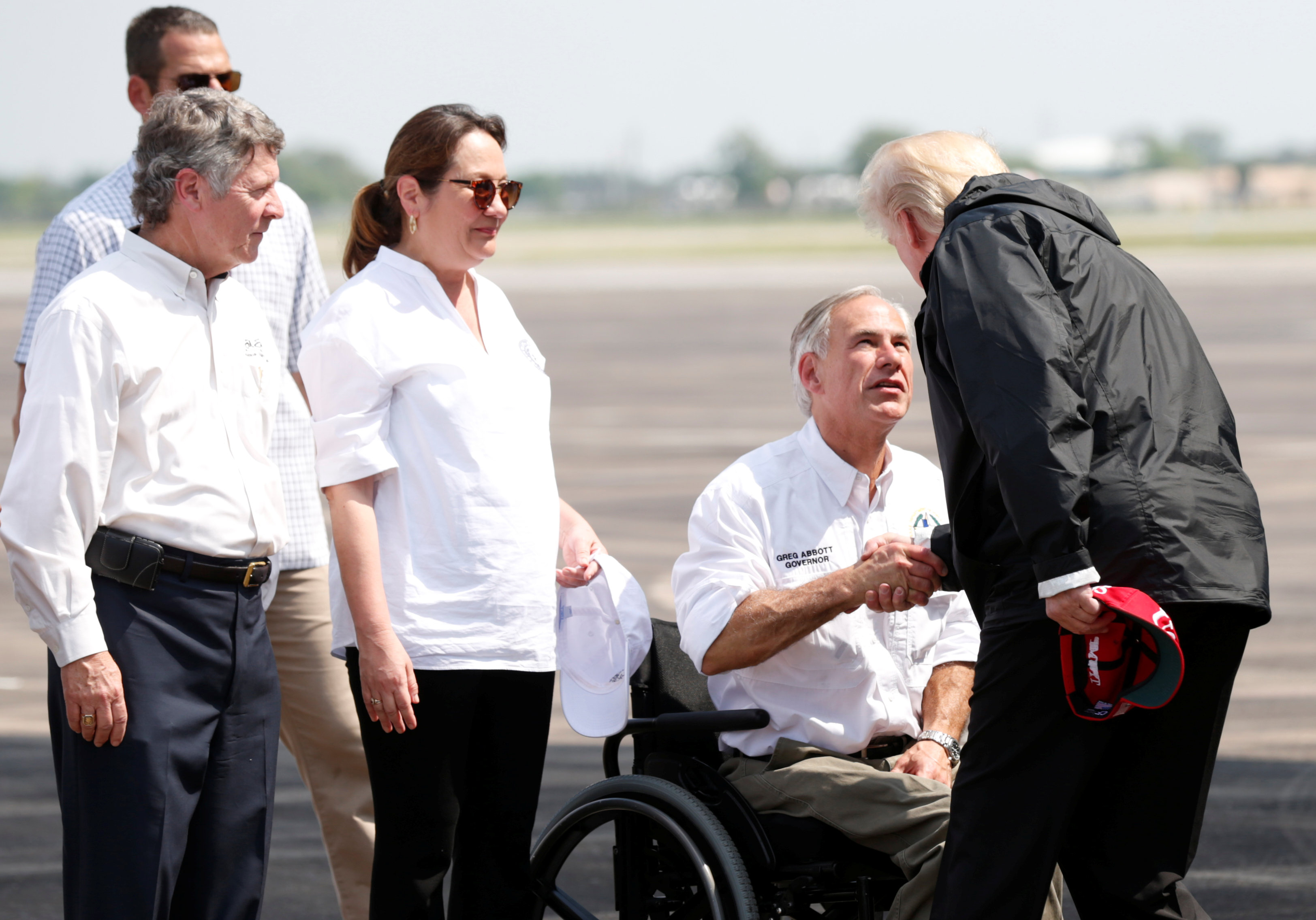 U.S. President Donald Trump greets Texas Governor Greg Abbott after arriving at Ellington Field to meet with flood survivors and volunteers who assisted in relief efforts in the aftermath of Hurricane Harvey, in Houston, Texas, U.S., September 2, 2017.   REUTERS/Kevin Lamarque