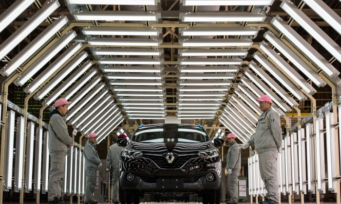 Chinese workers stand next to a Renault car on a production line of the Renault-Dongfeng factory in Wuhan, Hubei Province, on Feb. 1, 2016. (Johannes Eisele/AFP/Getty Images)