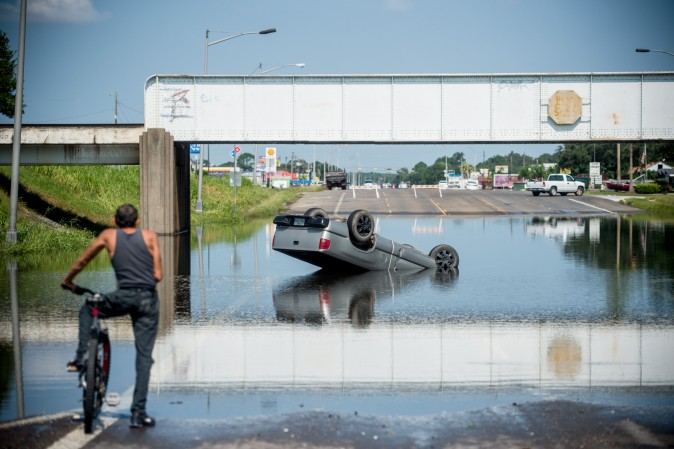 A bicyclist stops to look at a truck flipped into floodwater in Port Arthur in Houston on on Sept. 1. Houston was limping back to life on Friday one week after Hurricane Harvey slammed into America's fourth-largest city and left a trail of devastation across other parts of southeast Texas. (Emily Kask     /AFP/Getty Images)