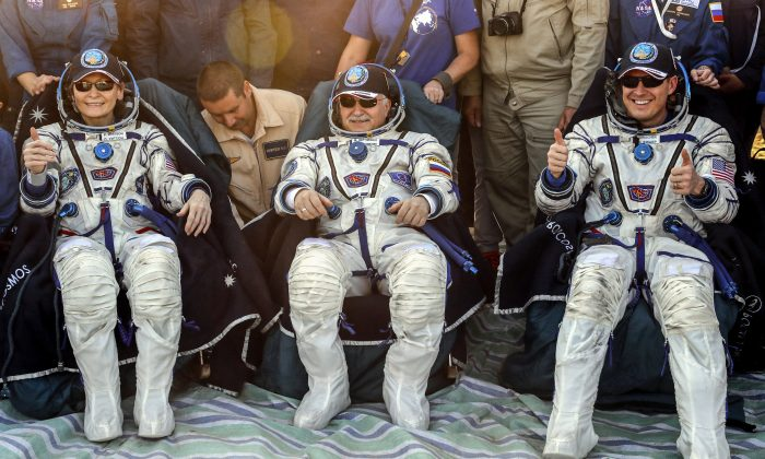 Members of the International Space Station (ISS) crew Peggy Annette Whitson of the U.S. (L), Fyodor Yurchikhin of Russia (C), and Jack Fischer of the U.S. rest shortly after the landing of the Soyuz MS-04 capsule in a remote area outside the town of Dzhezkazgan (Zhezkazgan), Kazakhstan September 3, 2017. (Reuters/Sergei Ilnitsky/Pool)