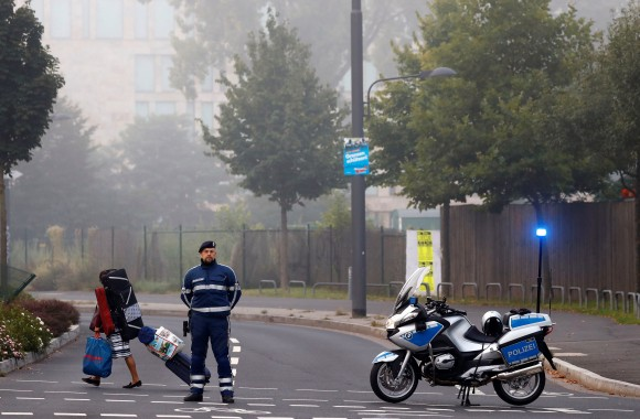 A woman carries her belongings walking past a police officer as some 60,000 people in Germany's financial capital are about to evacuate the city while experts defuse an unexploded British World War Two bomb found during renovations on the university's campus in Frankfurt, Germany, September 3, 2017.  (Reuters/Kai Pfaffenbach)
